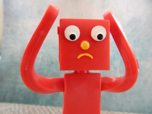 Image of a red Gumby figure with its arms up with a confused look on its face