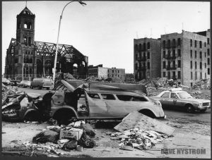 Image of the South Bronx in the 1980's with abandoned cars and buildings