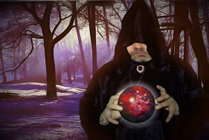 image of a black cloaked magician in the forest holding a red glowing sphere